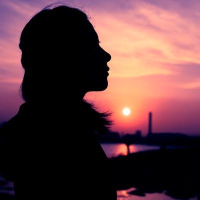 「紫色の夕焼けと女性のシルエット」の写真素材