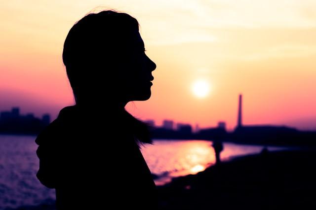 沈む夕日と女性のシルエットの写真