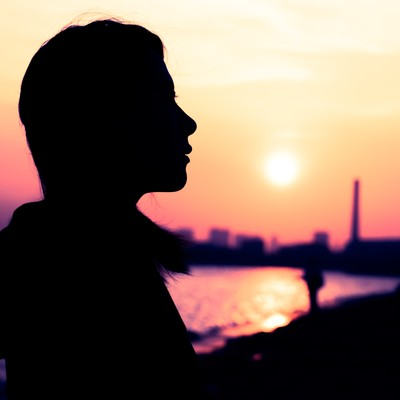 「沈む夕日と女性のシルエット」の写真素材