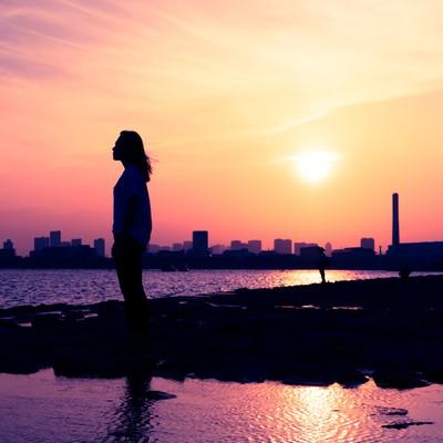 「夕焼けと黄昏れる女性のシルエット」の写真素材
