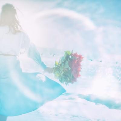 海辺で花束を持つ女性(フォトモンタージュ)の写真