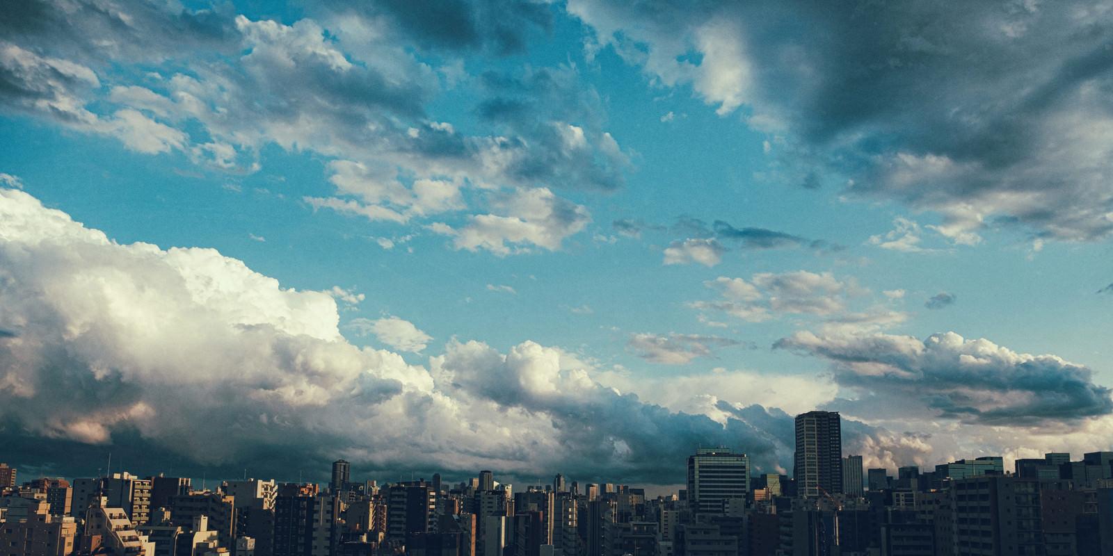 「上空に晴れ間と雨雲の街並み」の写真