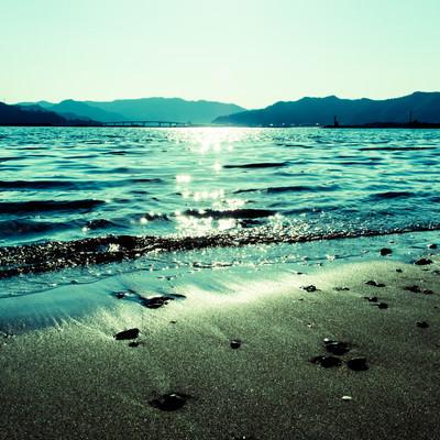 「日の光が差し込む浜辺」の写真素材