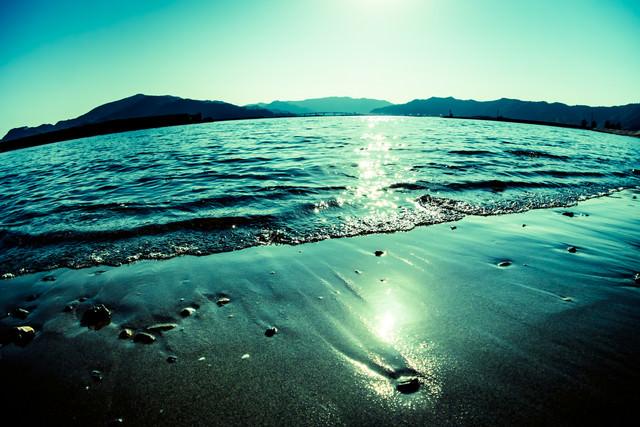 波打ち気際と日の光の写真
