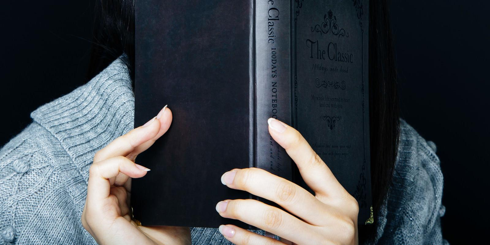「洋書を手に取る女性」の写真