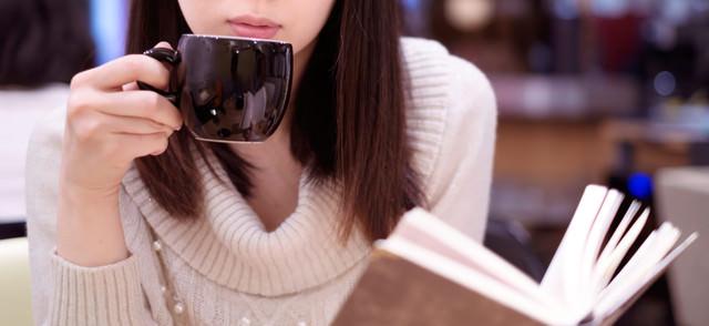 カフェでコーヒーを飲みながら読書女子の写真