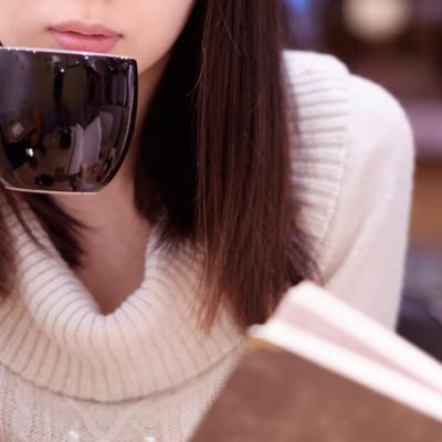 「カフェでコーヒーを飲みながら読書女子」の写真素材