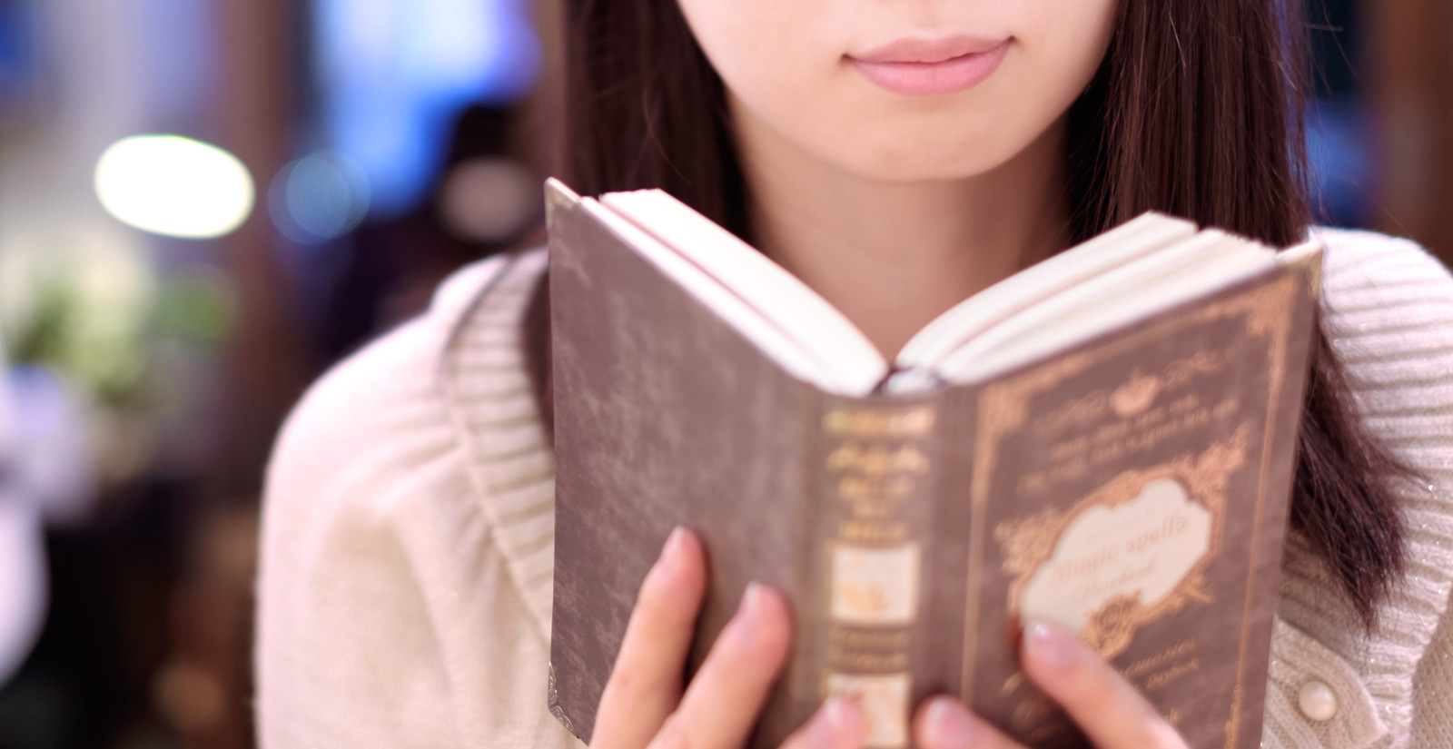 「カフェで洋書を読む女性」の写真