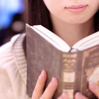 カフェで洋書を読む女性の写真