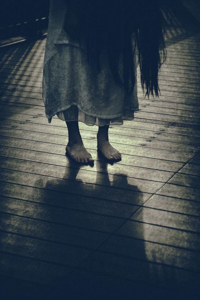 不気味な裸足の女性
