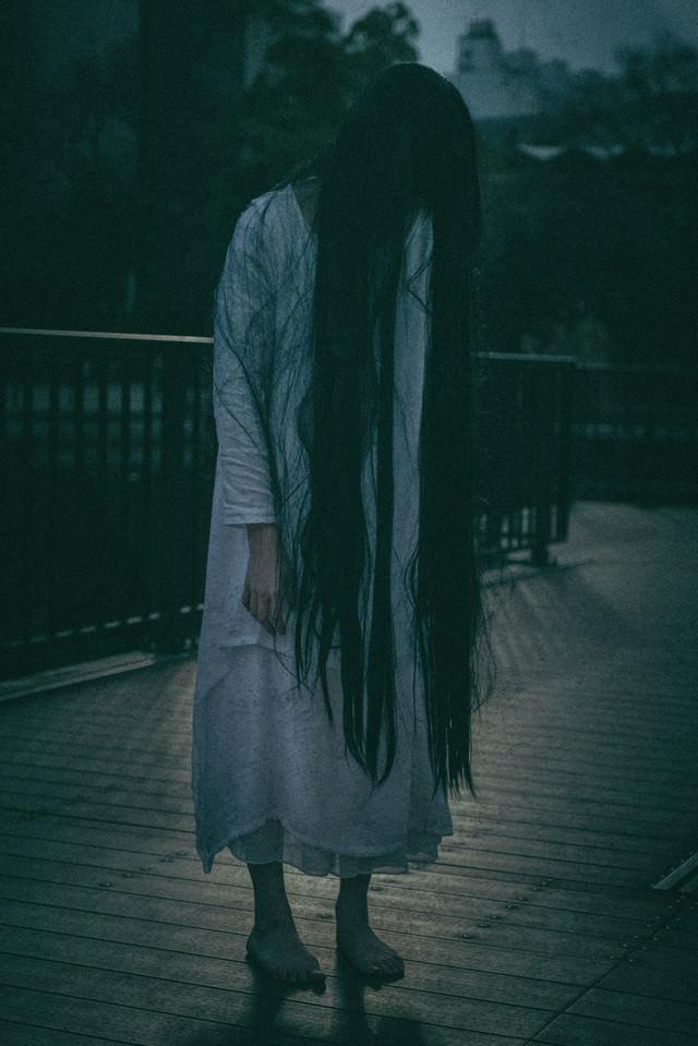 仄暗い闇に佇む女性の写真