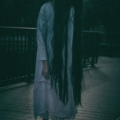 「仄暗い闇に佇む女性」の写真素材