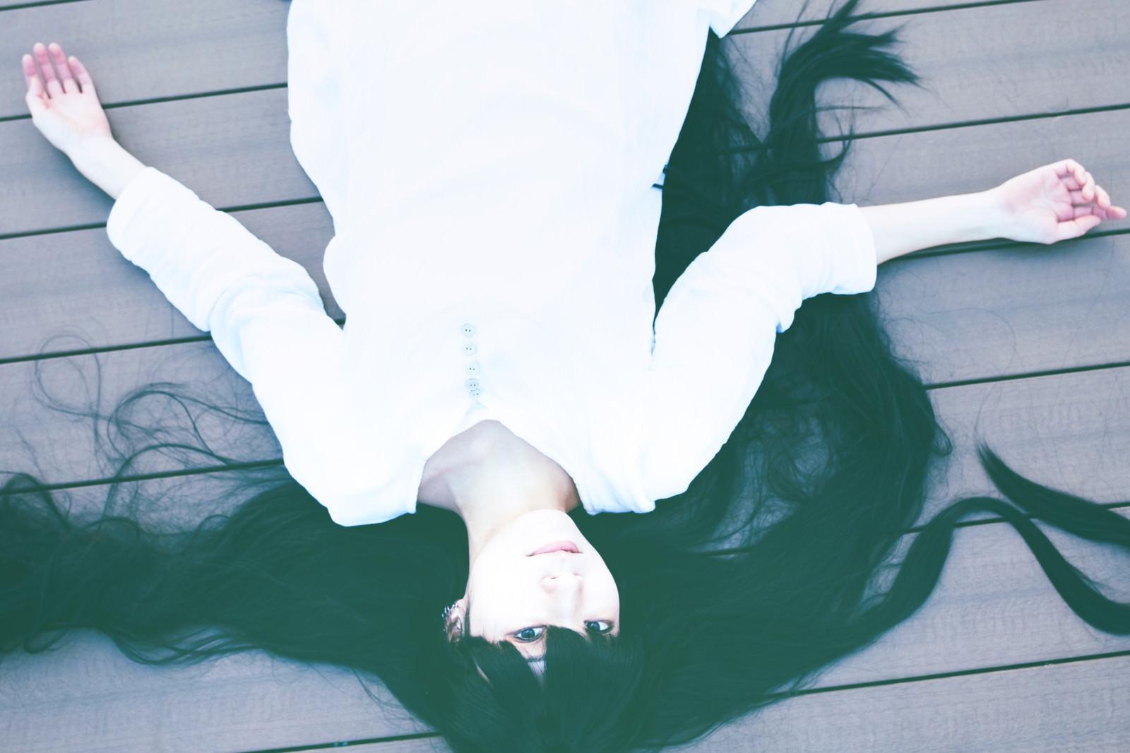 「床に倒れ込む髪の長い女性」の写真[モデル:緋真煉]