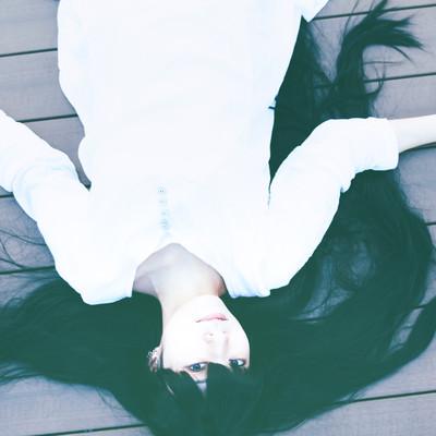 床に倒れ込む髪の長い女性の写真