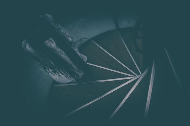 螺旋階段に立ちすくむ不気味な女性の姿の写真