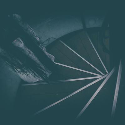 「螺旋階段に立ちすくむ不気味な女性の姿」の写真素材