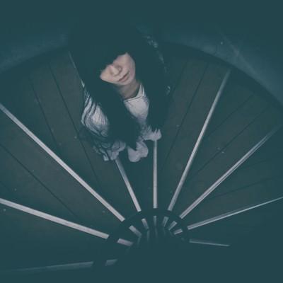 どこまでも続く螺旋階段を見上げる女性の写真