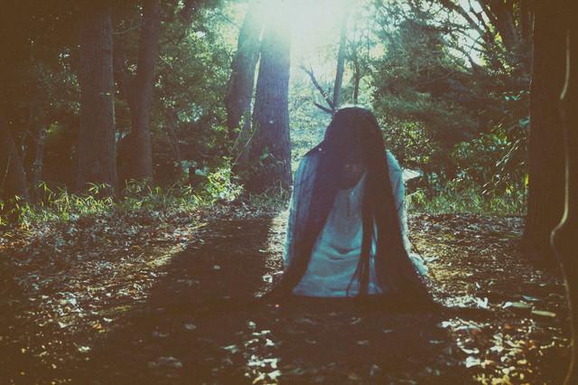 森の中で蹲りながら近づいてくる女性の写真