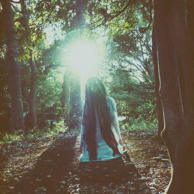 森の中で首をもたげる女性の写真