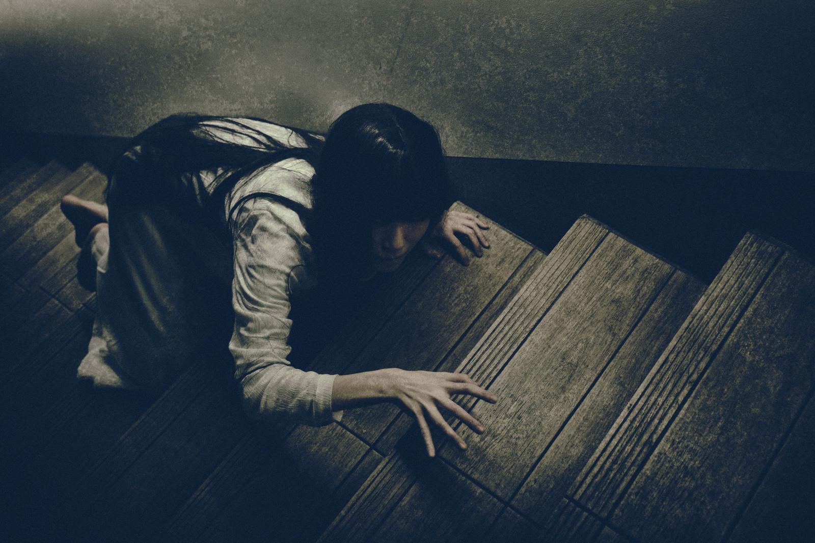 「物音を立てないように階段を上る女性」の写真[モデル:緋真煉]