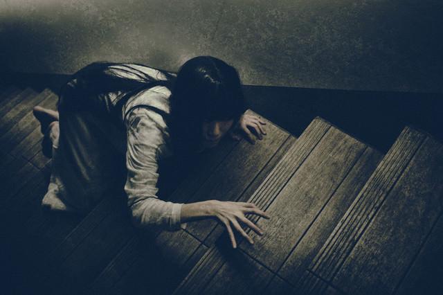 物音を立てないように階段を上る女性の写真