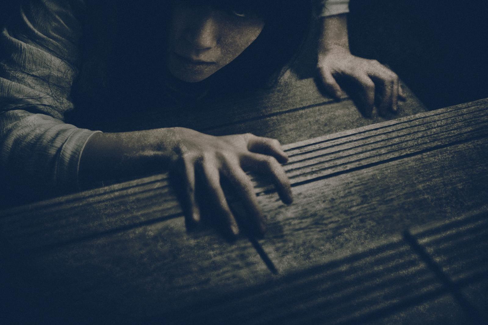 「階段に爪を立ててこちらを睨みつける女性」の写真[モデル:緋真煉]