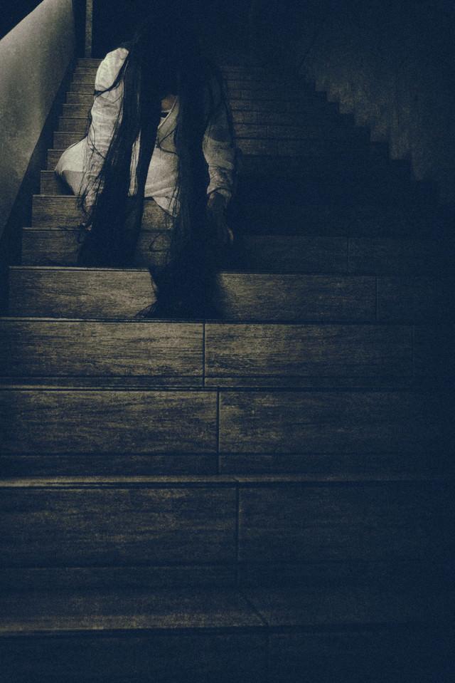 階段に座り込み垂れ下がる髪の毛を気にする女性の写真