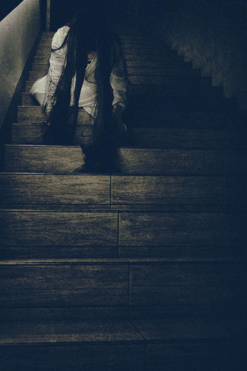「階段に座り込み垂れ下がる髪の毛を気にする女性」の写真[モデル:緋真煉]