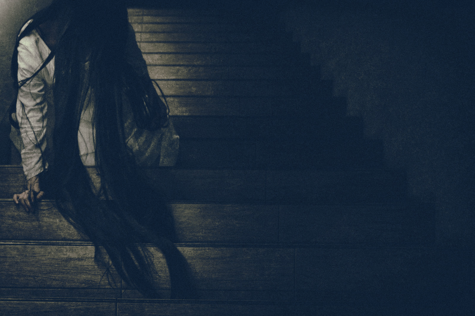 「髪の毛を垂れ下げ階段に居座る女性」の写真[モデル:緋真煉]
