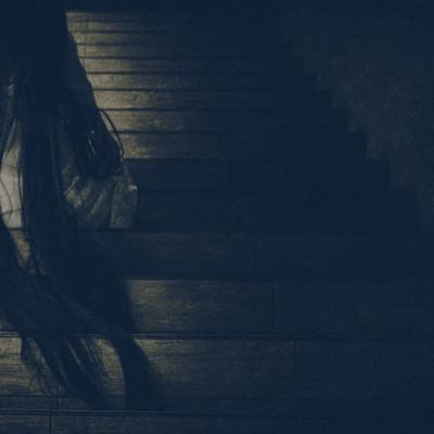髪の毛を垂れ下げ階段に居座る女性の写真