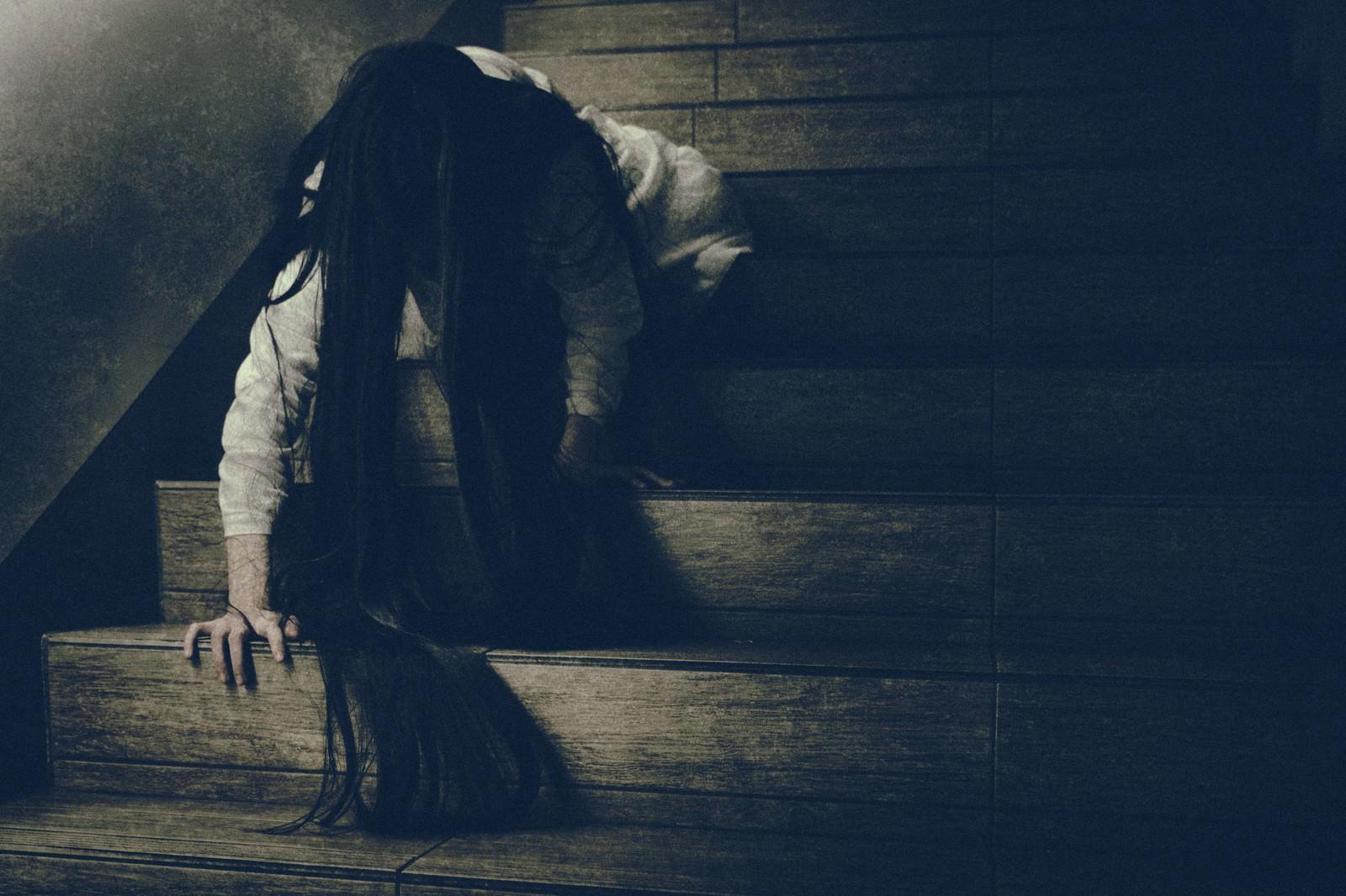 「階段を這って降りてくる髪の長い女性」の写真[モデル:緋真煉]