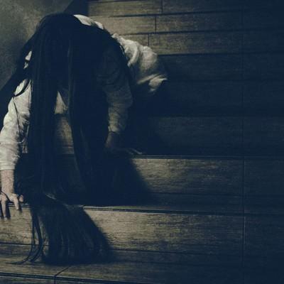 「階段を這って降りてくる髪の長い女性」の写真素材