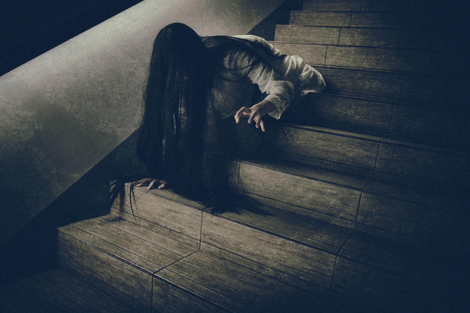 「階段を下りるのに伸びた髪が邪魔になる女性」の写真[モデル:緋真煉]