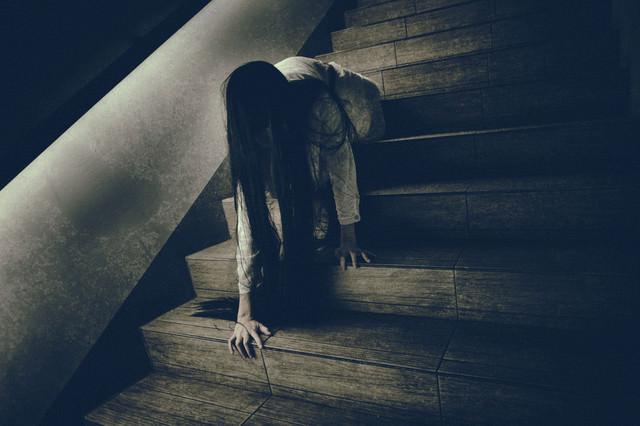 階段に座った状態からゆっくりと首を擡げようとする女性の写真