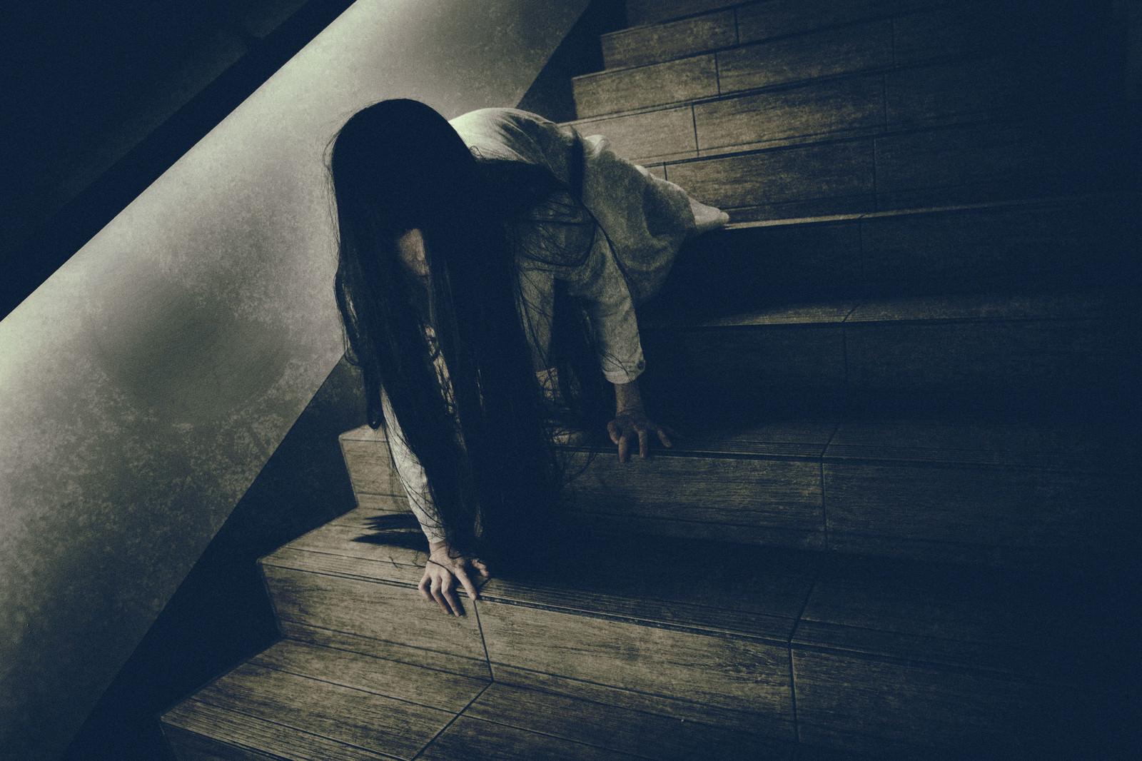 「ゆっくりとこちらを睨みつけようとする階段で蹲る女性」の写真[モデル:緋真煉]