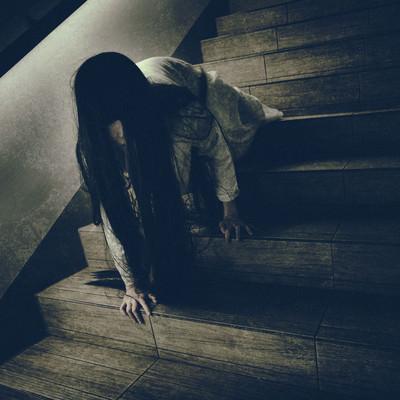 ゆっくりとこちらを睨みつけようとする階段で蹲る女性の写真