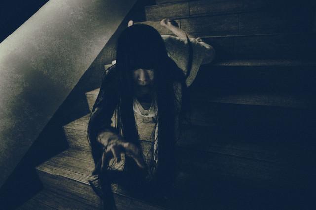 階段を這い降りながらこちらに手を伸ばす女性の写真