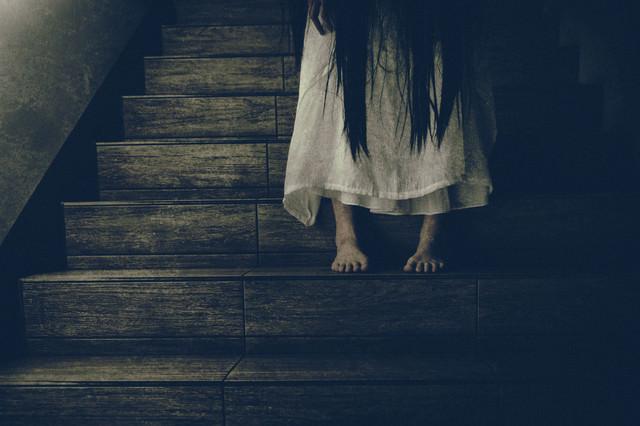 薄暗い階段に佇む女性の足元の写真