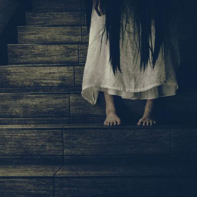 「薄暗い階段に佇む女性の足元」の写真素材