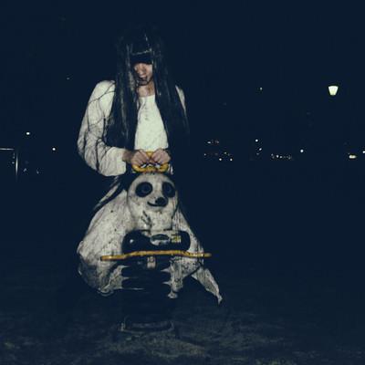夜の公園でパンダ遊具で楽しむ髪の長い女性の写真