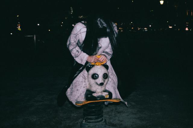 深夜の公園でパンダのスプリング遊具に乗った気味の悪い女性の写真