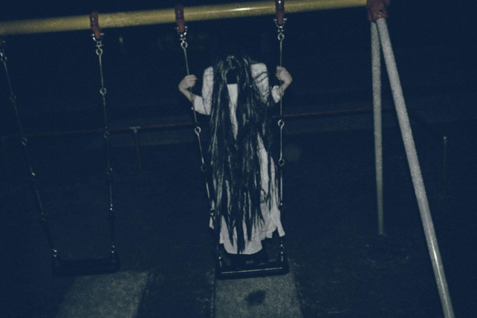 「夜の公園で立ちこぎに夢中な髪の長い女性」の写真[モデル:緋真煉]