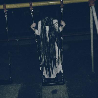 夜の公園で立ちこぎに夢中な髪の長い女性の写真