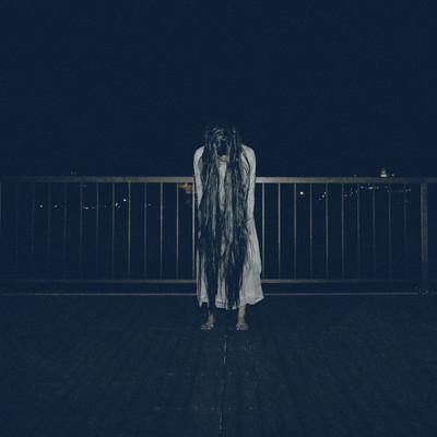 真夜中の公園で裸足で佇む女性の写真