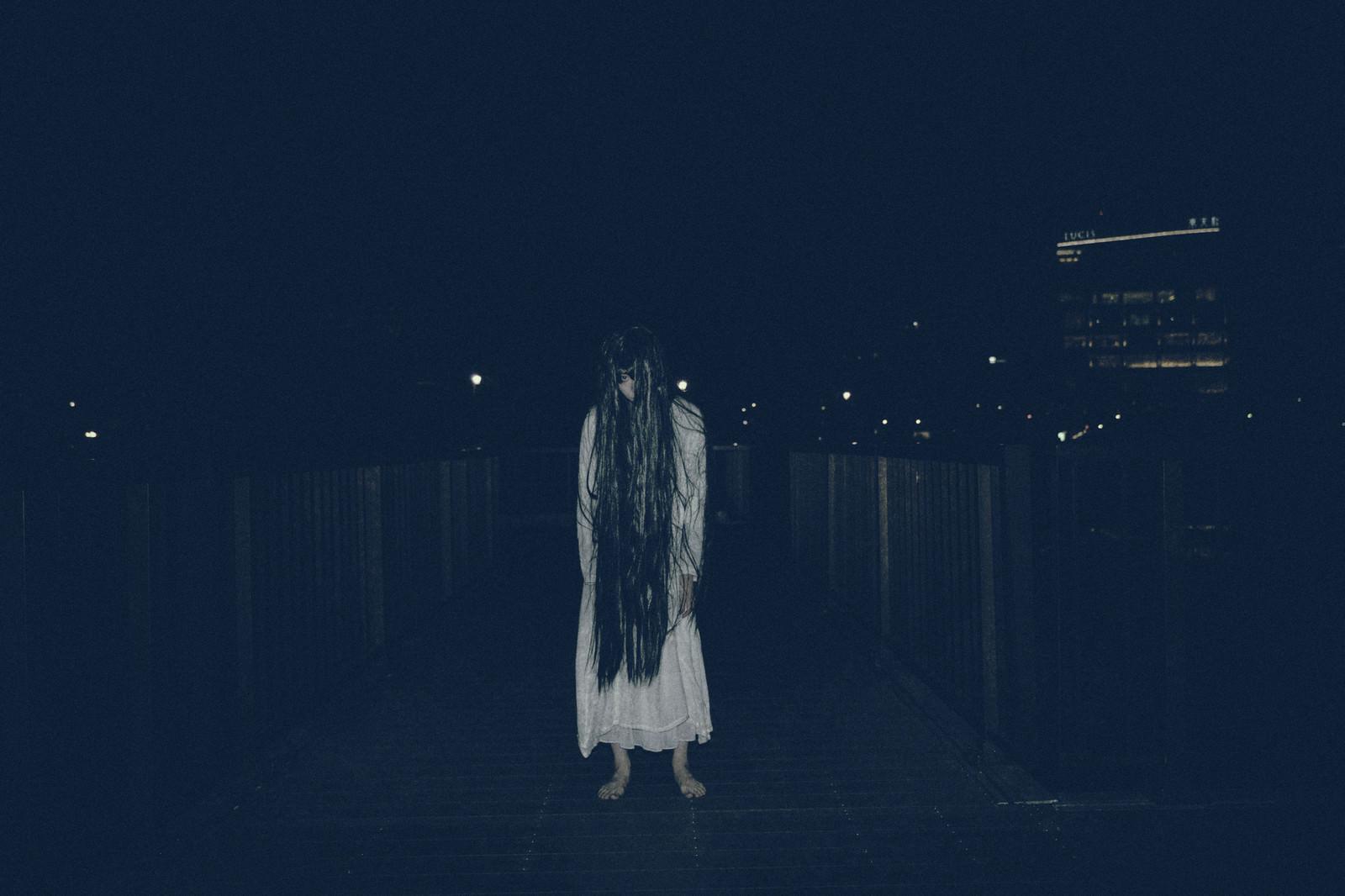 「暗闇に立ちすくむ長髪の女性」の写真[モデル:緋真煉]
