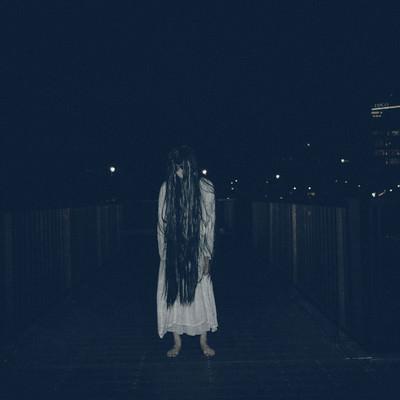 暗闇に立ちすくむ長髪の女性の写真