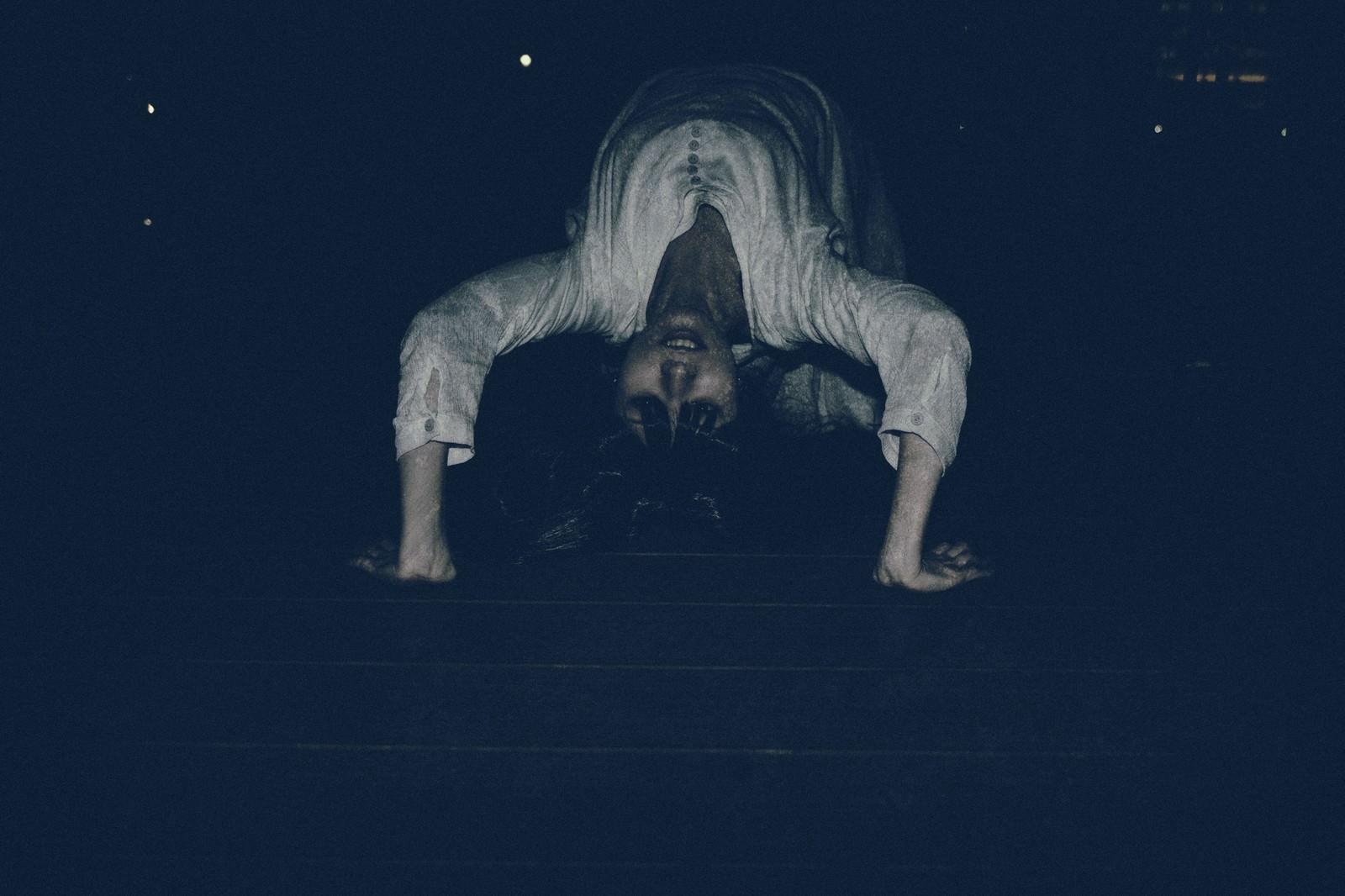 「悪魔にとり憑かれ暗闇の中ブリッジで追いかけてくる女性」の写真[モデル:緋真煉]