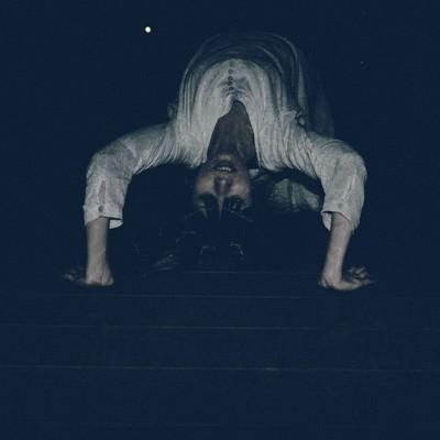 「悪魔にとり憑かれ暗闇の中ブリッジで追いかけてくる女性」の写真素材