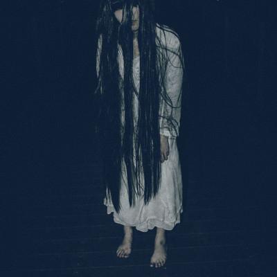 長い髪を垂れ下げてこちらに近づく女性の写真