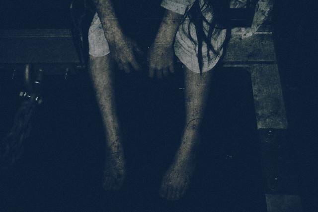 座り込んで手足をぶら下げる女性の姿の写真
